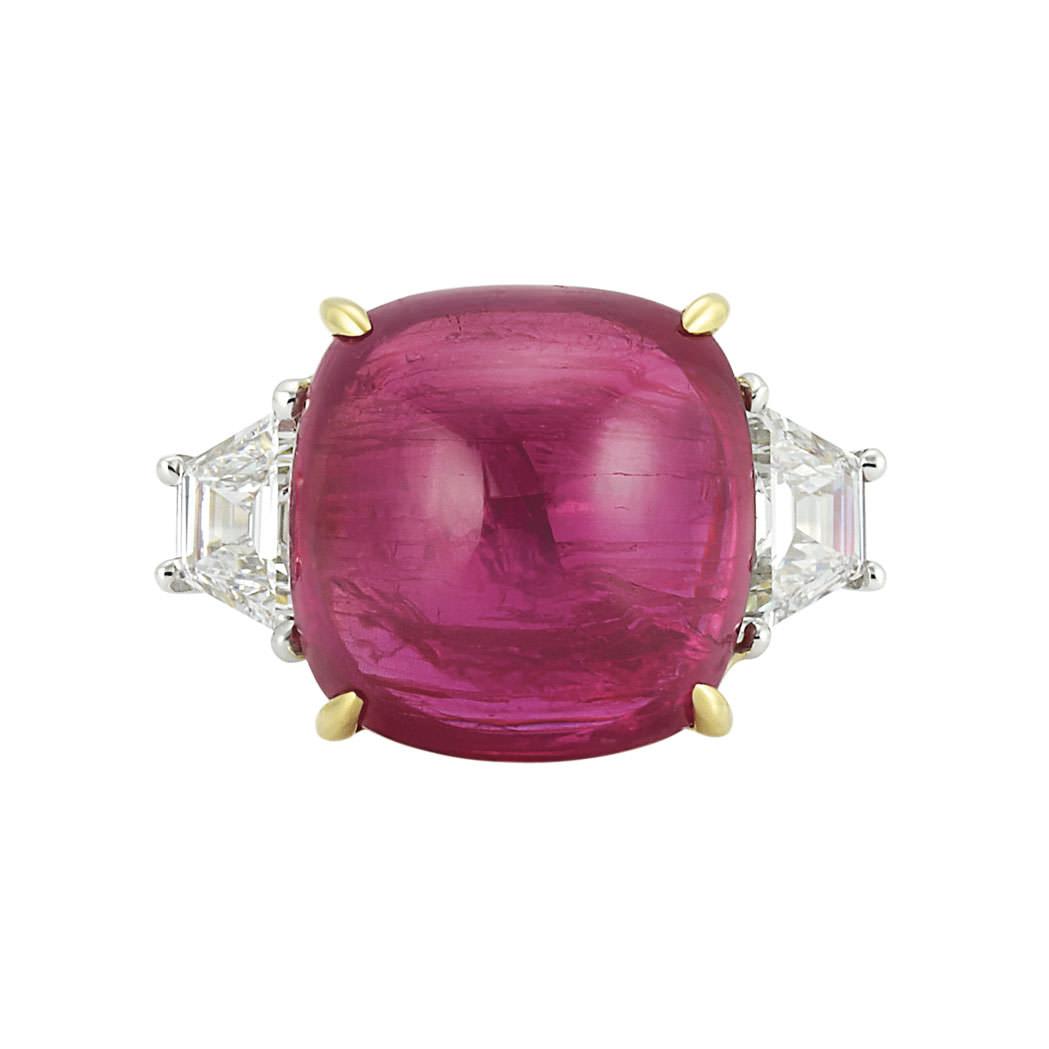 Anillo con rubí en cabujón de aprox.16 qts, flanqueado por 2 diamantes engastados en platino y oro - estimado entre $15.000 y $2